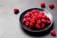 Fresh raspberries on a black bowl Slate background.  Royalty Free Stock Images