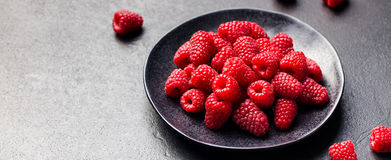 Fresh raspberries on a black bowl Slate background.  Royalty Free Stock Photography