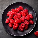 Fresh raspberries on a black bowl. Slate background. Top view. Fresh raspberries on a black bowl. Slate background Top view Stock Image