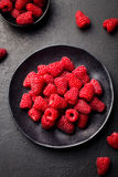 Fresh raspberries on a black bowl. Top view. Fresh raspberries on a black bowl. Stone background. Top view Stock Photo