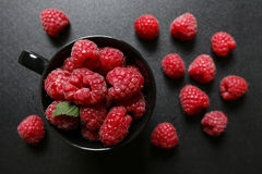 Fresh raspberries in a black cup. On black background Royalty Free Stock Images