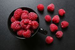 Fresh raspberries in a black cup. On black background Royalty Free Stock Photos