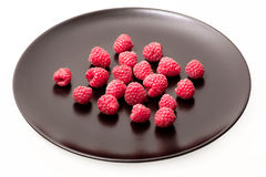 Fresh raspberries on black plate. White background Royalty Free Stock Image