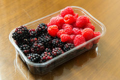 Fresh raspberries and blackberries. Close up of fresh raspberries and blackberries in plastic container Stock Photos