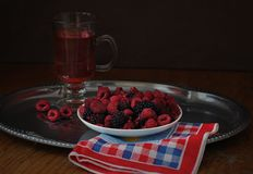 Fresh raspberries and blackberries and a glass of raspberry juice. On a dark background Royalty Free Stock Photos