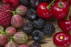Fresh raspberries,  blackberries, gooseberry and cherry. Fresh raspberries, blackberries, gooseberry and cherry on a wooden background Stock Image