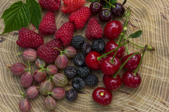 Fresh raspberries,  blackberries, gooseberry and cherry. Fresh raspberries, blackberries, gooseberry and cherry on a wooden background Stock Photo