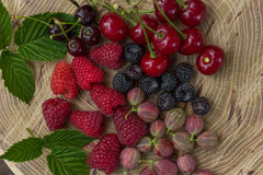 Fresh raspberries,  blackberries, gooseberry and cherry. Fresh raspberries, blackberries, gooseberry and cherry on a wooden background Royalty Free Stock Photo