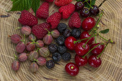 Fresh raspberries,  blackberries, gooseberry and cherry. Fresh raspberries, blackberries, gooseberry and cherry on a wooden background Royalty Free Stock Photography