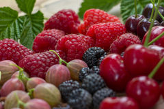 Fresh raspberries,  blackberries, gooseberry and cherry. Fresh raspberries, blackberries, gooseberry and cherry on a wooden background Royalty Free Stock Images