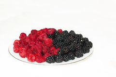 Fresh raspberries and blackberries on plate, symbol of yin and yang. Fresh raspberries and blackberries on plate lined with symbol of yin and yang on red Stock Photos