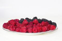 Fresh raspberries and blackberries on plate, symbol of yin and yang. Fresh raspberries and blackberries on plate lined with symbol of yin and yang on red Royalty Free Stock Photo