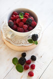 Fresh  raspberries and blackberries. In a white plate on old wooden background, selective focus Stock Image