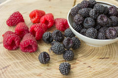 Fresh raspberries and blackberries. On a wooden background Stock Photo