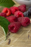 Fresh raspberries and blackberries. On a wooden background Stock Image