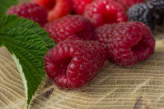 Fresh raspberries and blackberries. On a wooden background Royalty Free Stock Photography