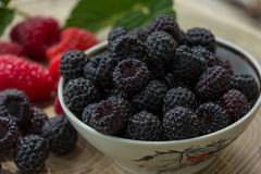 Fresh raspberries and blackberries. On a wooden background Royalty Free Stock Images