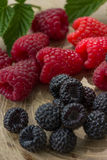 Fresh raspberries and blackberries. On a wooden background Stock Photography