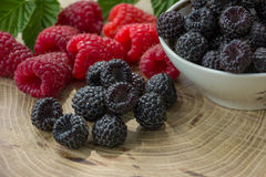Fresh raspberries and blackberries. On a wooden background Stock Images