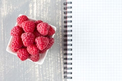 Fresh raspberries and blank notebook. For recording Stock Images