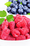 Fresh raspberries and blueberries. In the background Stock Photo