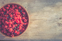 Fresh raspberries and blueberries in a bowl. Bowl with raspberries and blueberries in the evening light, copy space. Filtered image Stock Photography