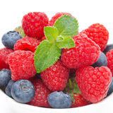 Fresh raspberries and blueberries, closeup. Fresh raspberries and blueberries on white, closeup Royalty Free Stock Image