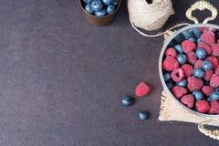 Fresh raspberries and blueberries dark picture with copy space on left. Fresh fruits, berries in an old copper cup, bowl. Dark Sty. Led Stock Photo, Black Stock Photography