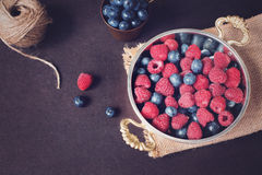 Fresh raspberries and blueberries dark picture with copy space on left. Fresh fruits, berries in an old copper cup, bowl. Dark Sty Royalty Free Stock Image