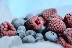 Fresh raspberries and blueberries are frozen on cold blue ice. Fresh raspberries and blueberries are frozen on cold blue ice Stock Image