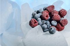 Fresh raspberries and blueberries are frozen on cold blue ice. Fresh raspberries and blueberries are frozen on cold blue ice Royalty Free Stock Photos