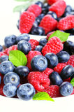 Fresh raspberries and blueberries mixed. On a white background Royalty Free Stock Image