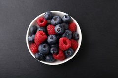 Fresh raspberries and blueberries in a plate. Berries Stock Photography