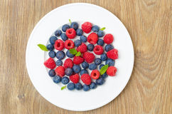 Fresh raspberries and blueberries on a plate on a wood. En background, top view, horizontal Stock Photo