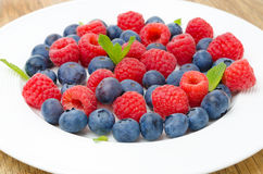 Fresh raspberries and blueberries on a plate. On a wooden background Stock Photos