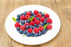 Fresh raspberries and blueberries on a plate on a wooden table. Close-up Royalty Free Stock Images