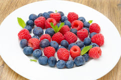 Fresh raspberries and blueberries on a plate on a wooden table. Horizontal close-up Stock Images