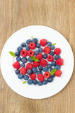 Fresh raspberries and blueberries on a plate on a wooden table. Top view vertical Stock Images