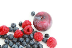 Fresh raspberries, blueberries and plum. Over white Stock Photos