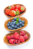 Fresh raspberries, blueberries and strawberries in a wooden bowl. S, isolated on white Royalty Free Stock Images