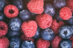 Fresh raspberries and blueberries top view background. Vintage toned Royalty Free Stock Images