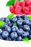 Fresh raspberries and blueberries. On white background Royalty Free Stock Photos