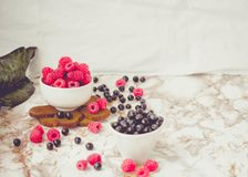 Fresh raspberries and blueberries in white cups. white marble ba. Ckground. Summer fruit, berries. Detox diets and healthy food concept.Toning.Place for text Stock Image