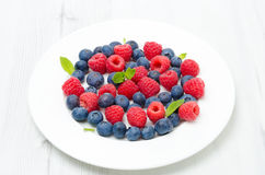 Fresh raspberries and blueberries on a white plate. Fresh raspberries and blueberries on the plate on a white table Stock Image