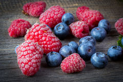 Fresh raspberries and blueberries on wooden table.  Stock Photo