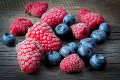 Fresh raspberries and blueberries on wooden table.  Royalty Free Stock Photo