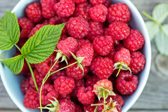 Fresh raspberries in a bowl. On a wooden table Stock Image