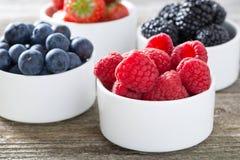Fresh raspberries in a bowl and berries, closeup, horizontal Stock Photos
