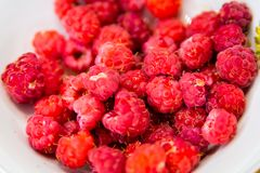 Fresh raspberries in bowl, closeup. Red fresh raspberries in white bowl, closeup Stock Images