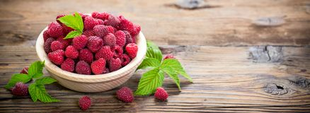 Fresh raspberries in the bowl. On the wooden table Stock Photography